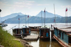 boats is Laos with mountains in the background   Stephen Leonardi -Unsplash